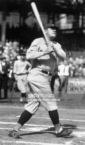 New York Yankees Babe Ruth swinging his bat and follows flight of one of his home runs circa 1925