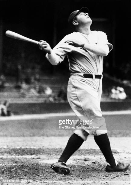 New York Yankees Babe Ruth swinging his bat and follows flight of the ball circa 1925