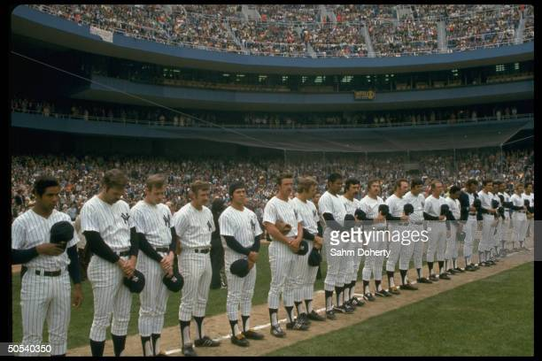 New York Yankees baseball team standing in row on first base line while holding caps in hand for the singing of the National Anthem during opening...