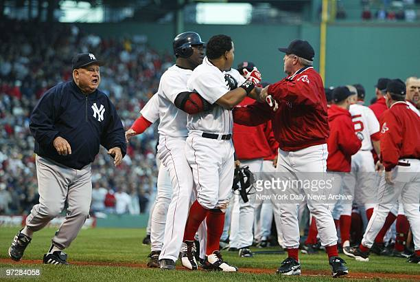 New York Yankees' bench coach Don Zimmer races towards Boston Red Sox' pitcher Pedro Martinez as Red Sox' David Ortiz and manager Grady Little...