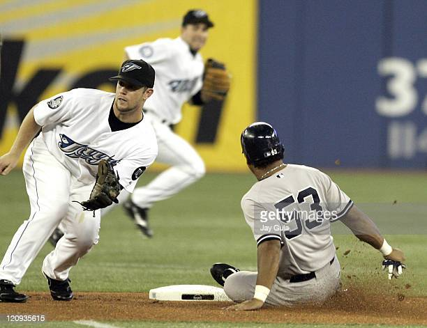 New York Yankees Bobby Abreu slides into 2nd base safely with a stolen base ahead of the tag from Toronto 2nd baseman Aaron Hill in action vs the...