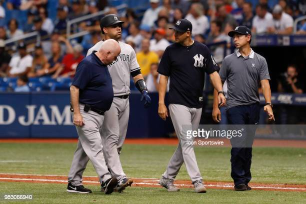 New York Yankees catcher Gary Sanchez walks off the field with New York Yankees manager Aaron Boone Trainer Steve Donohue and Yankees Spanish...