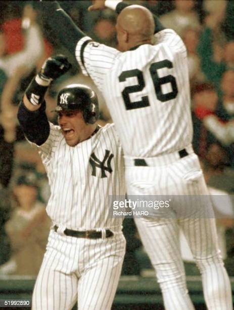 New York Yankees catcher Jim Leyritz exults as he is jumped on at homeplate by teammate Darryl Strawberry after hitting a tworum homerun in the...