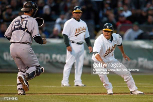 New York Yankees' catcher Jorge Posada chases Oakland Athletics' Kurt Suzuki on rundown between third and home plate in the second inning of their...