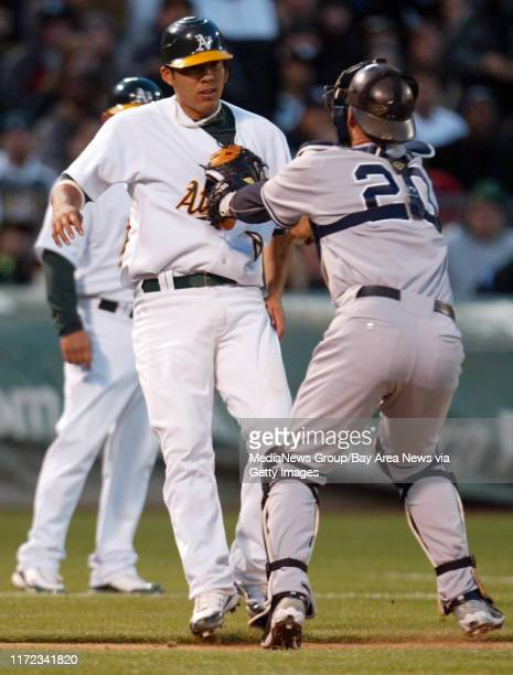New York Yankees catcher Jorge Posada tags out Oakland Athletics Kurt Suzuki on rundown between third and home plate in the second inning of their...