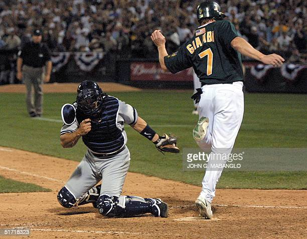 New York Yankees' catcher Jose Posada tags out Oakland Athletics' Jeremy Giambi at homeplate from scoring the tying run during the eight inning 13...