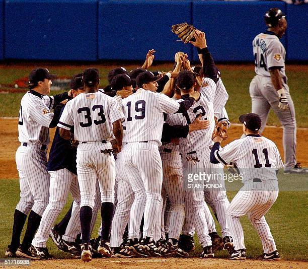 New York Yankees celebrate their win over the Seattle Mariners as Mariners Mike Cameron walks off the field after the American League Championship...