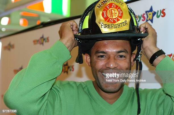 New York Yankees' closing pitcher Mariano Rivera tries on his new FDNY honorary firefighter's helmet during the annual Uniformed Firefighters...