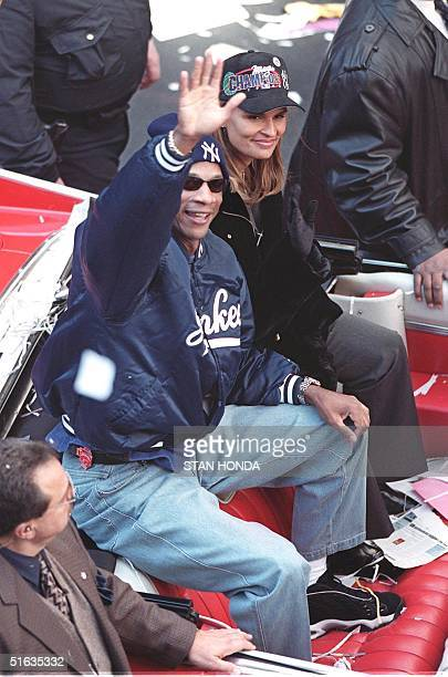 New York Yankees' Darryl Strawberry who sat out the postseason after undergoing colon cancer surgery rides up Broadway in New York City with his wife...