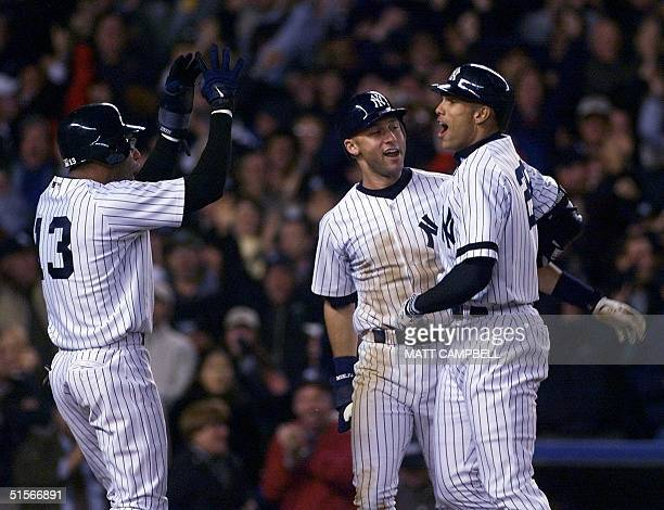New York Yankees David Justice celebrates with teammates Derek Jeter and Jose Vizcaino after hitting a threerun home run in the seventh inning...