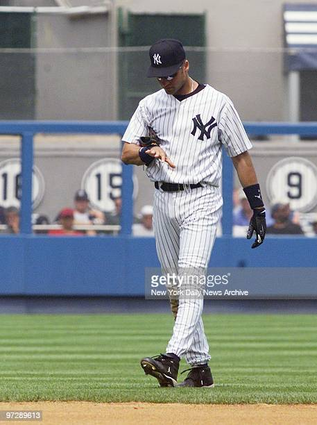 New York Yankees' Derek Jeter checks his hand after getting clipped while trying to field a grounder in game against the Detroit Tigers at Yankee...