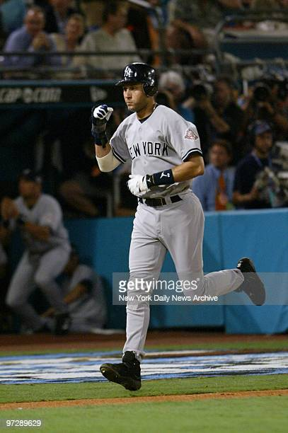 New York Yankees' Derek Jeter clenches his fist as he heads home after a basesloaded walk in the fourth inning of Game 3 of the World Series against...