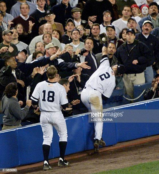 New York Yankees Derek Jeter goes into the fans to catch a foul ball in the 8th inning as teammate Scott Brosius watches during their game against...