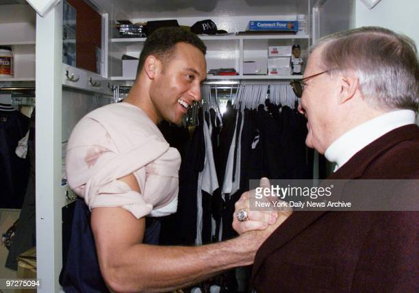 New York Yankees' Derek Jeter wearing an ice pack on his shoulder is congratulated in the locker room by principal owner George Steinbrenner after...
