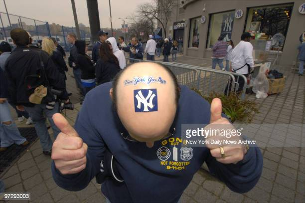 New York Yankees fan Barry Phillips gives two thumbsup for his team as he shows off the Yanks logo on top of his head while outside Yankee Stadium...