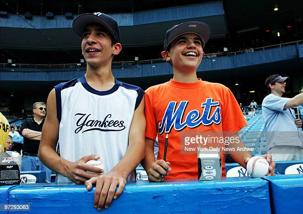 New York Yankees' fan Joe Andreani and his cousin New York Mets' fan Anthony Andreani both from Long Island watch batting practice before the start...