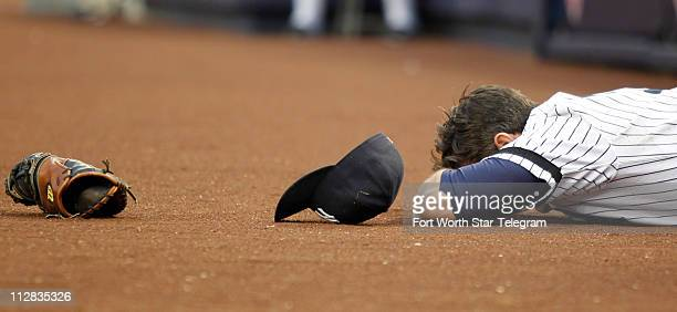 New York Yankees first baseman Lance Berkman goes down hard in pursuit of a foul ball in the seventh inning against the Texas Rangers in Game 5 of...