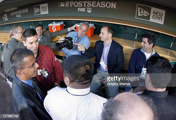 New York Yankees general manager Brian Cashman looks at a photo taken by photographer Jeff Kowalski while talking to the media prior to playing the...