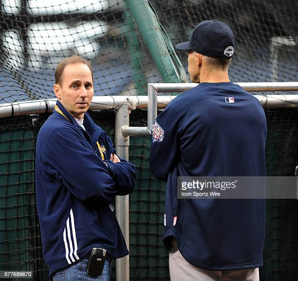 New York Yankees general manager Brian Cashman looks back as he talks with manager Joe Girardi during the teams practice a day before game three of...