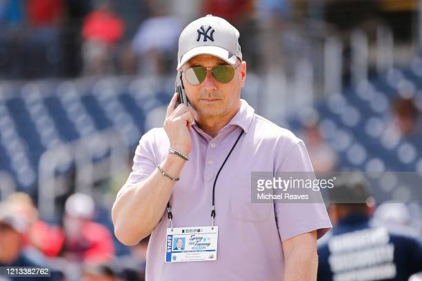 New York Yankees general manager Brian Cashman talks on the phone prior to a Grapefruit League spring training game between the Washington Nationals...