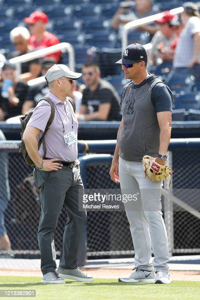 New York Yankees general manager Brian Cashman talks with manager Aaron Boone prior to a Grapefruit League spring training game against the...
