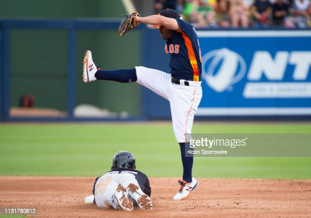 New York Yankees Infielder Gleyber Torres slides into second base under Houston Astros InfielderJose Altuve during an MLB spring training game...