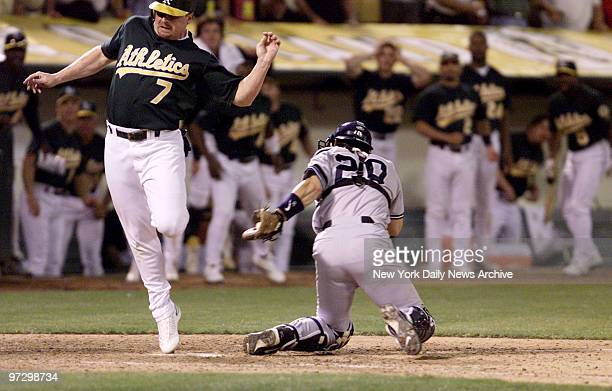 New York Yankees' Jorge Posada holds on to ball after sweep tag on Oakland Athletics' Jeremy Giambi during Game 3 of American League Division Series....