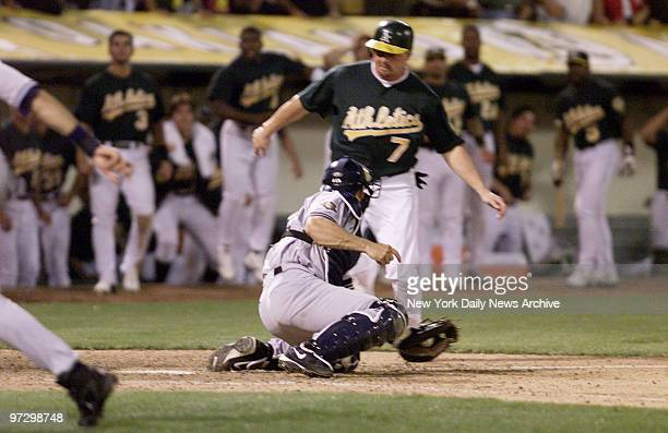 New York Yankees' Jorge Posada holds on to ball after sweep tag on Oakland Athletics' Jeremy Giambi during Game 3 of American League Division Series...