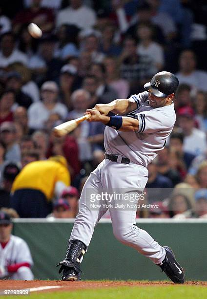 New York Yankees' Jorge Posada swats the ball to deep left center for a two RBI double in the fourth inning against the Boston Red Sox at Fenway Park...