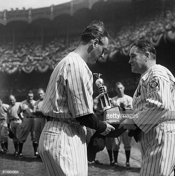 New York Yankees' manager Joe McCarthy presents Lou Gehrig with a trophy of behalf of the team following a game against the Senators at Yankee...