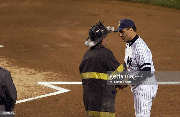 New York Yankees manager Joe Torre greets a New York City fire fighter during introductions prior to game one of their American League Division...