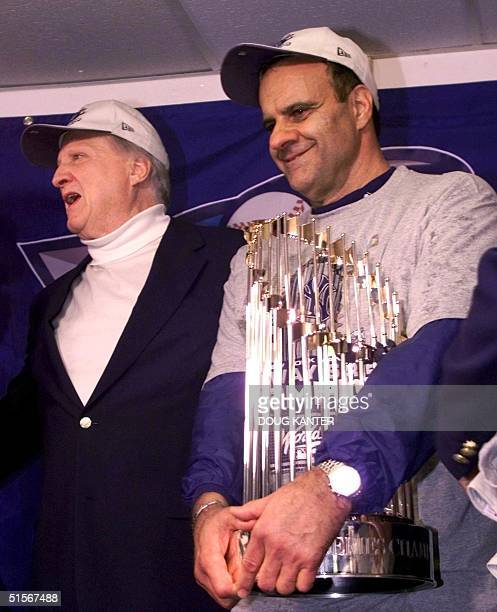 New York Yankees Manager Joe Torre holds the World Series trophy beside team owner George Steinbrenner in the team's locker room after the Yankees...