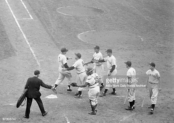 New York Yankees' Mickey Mantle is greeted by Yogi Berra Hank Bauer Joe Collins and Billy Martin after belting a grand slam homer in the fifth inning...