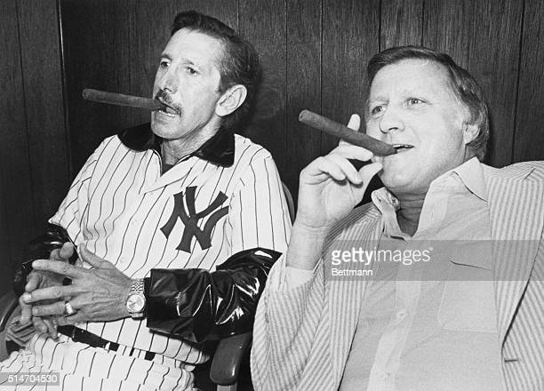 New York Yankees' owner George Steinbrenner and Billy Martin smoke cigars as they announce Martin's return as team manager