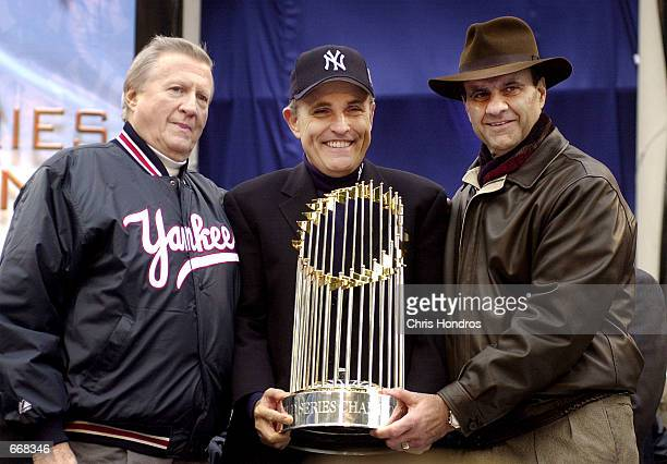 New York Yankees owner George Steinbrenner left New York Mayor Rudy Giuliani and Yankees manager Joe Torre right hold the World Series trophy October...
