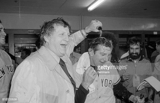 New York Yankees owner George Steinbrenner pours champagne over the head of his manager Billy Martin in the dressing room after the Yankees beat the...