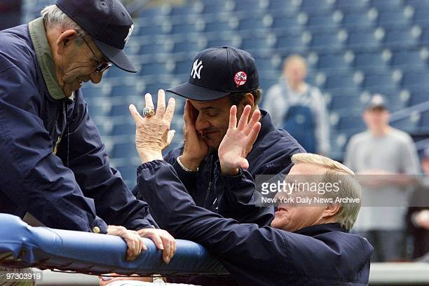 New York Yankees' owner George Steinbrenner talks with baseball great Yogi Berra and Yankees' manager Joe Torre as pitchers and catchers report on...