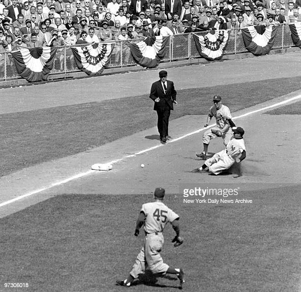 New York Yankees' Phil Rizzuto nears third base with two out in the third inning as third baseman Don Hoak tries to get to the grounder during World...