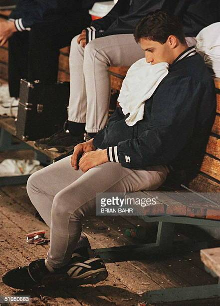 New York Yankees pitcher Andy Pettitte sits in the dugout holding a towel in his mouth as relief pitcher John Wetteland pitches the final two outs in...