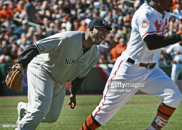 New York Yankees pitcher CC Sabathia left screams after he was unable to bare hand a slow grounder by Baltimore Orioles' Adam Jones right in the...