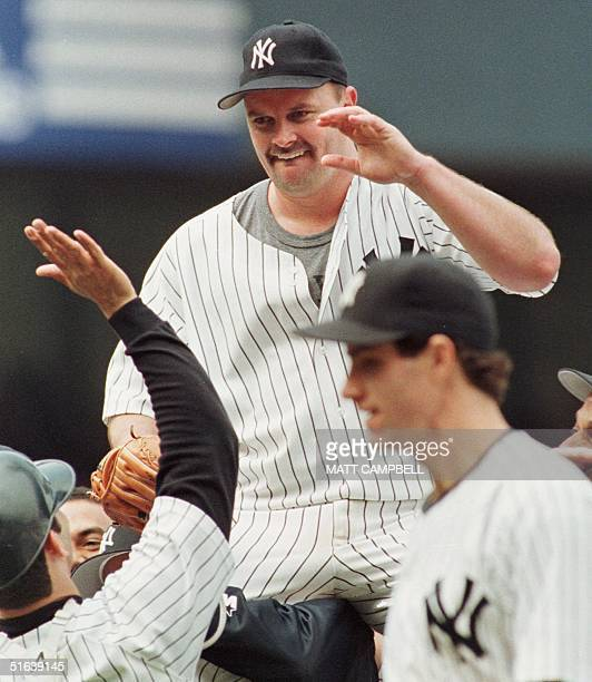 New York Yankees pitcher David Wells is carried off the field by his teammates after pitching a perfect game against the Minnesota Twins 17 May at...