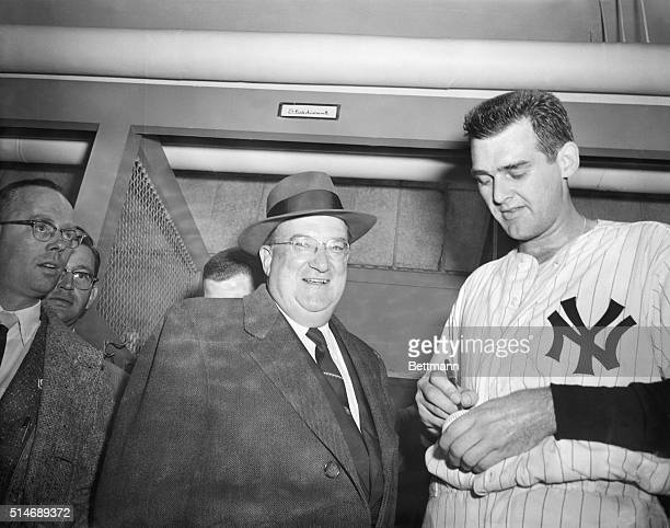 New York Yankees pitcher Don Larsen signs a baseball after becoming the first pitcher to pitch a perfect World Series game Walter O'Malley the owner...
