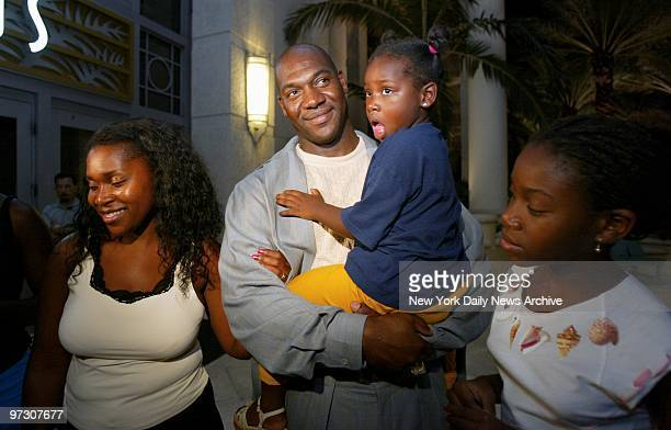 New York Yankees' pitcher Jose Contreras holds his 3yearold daughter Naylenis as wife Miriam and daughter Nayalan stand by at the Loews Hotel in...