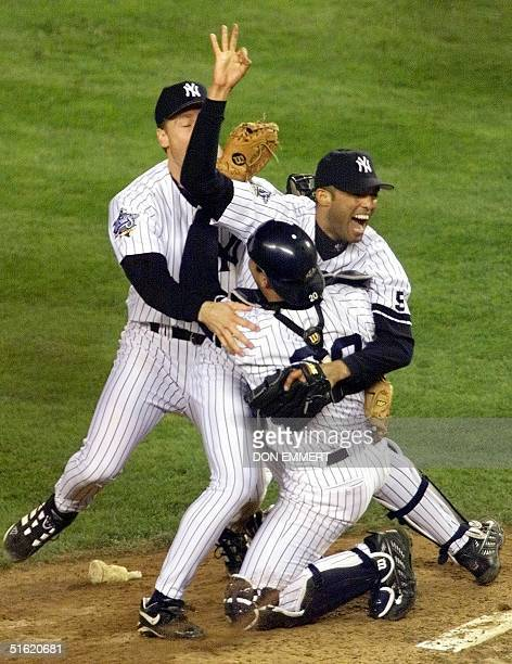 New York Yankees pitcher Mariano Rivera is rushed by teammates Scott Brosius and Jorge Posada on the pitcher's mound after the Yankees defeated the...