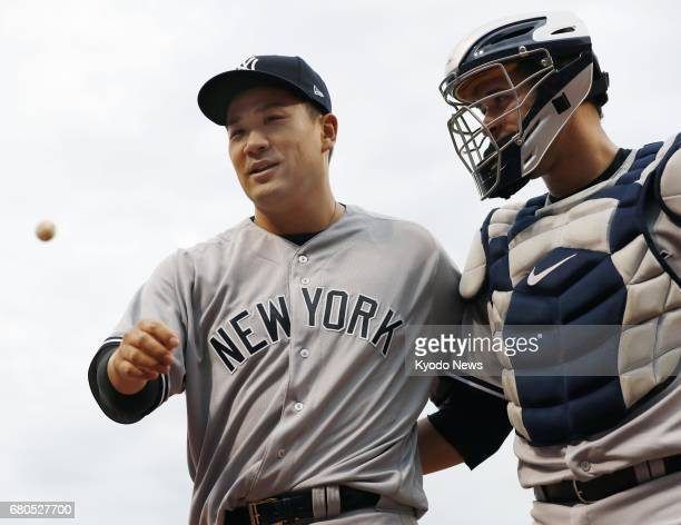 New York Yankees pitcher Masahiro Tanaka walks back to the dugout with catcher Gary Sanchez after ending the first inning against the Cincinnati Reds...
