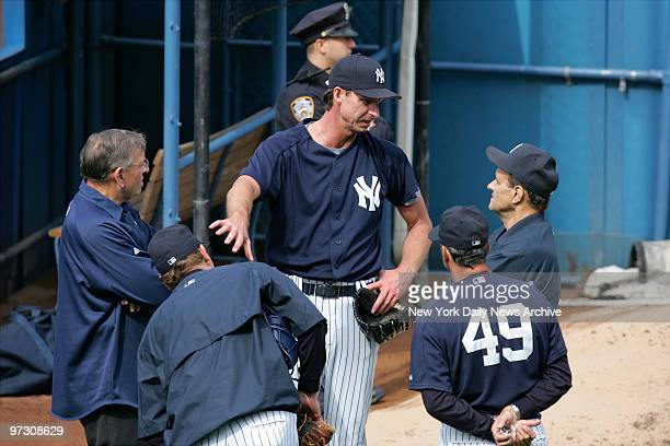 New York Yankees' pitcher Randy Johnson speaks with manager Joe Torre as pitching coach Ron Guidry and team physician Stuart Hershon look on during a...