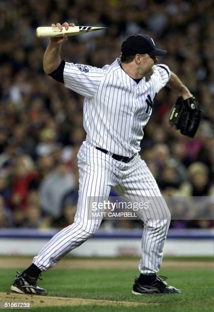 New York Yankees pitcher Roger Clemens throws the broken bat of Mike Piazza of the New York Mets as Piazza runs to first base during the first inning...