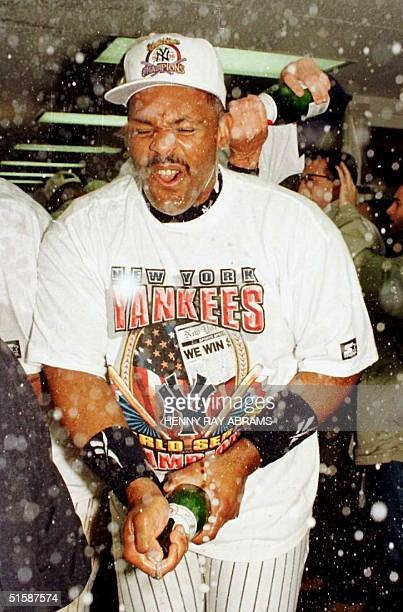 New York Yankees player Cecil Fielder sprays champagne in the locker room after the Yankees won the World Series 32 by beating the Atlanta Braves 26...