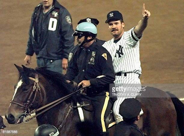 New York Yankees player Wade Boggs is given a ride around the field by New York City mounted police officer after the Yankees won the World Series 26...