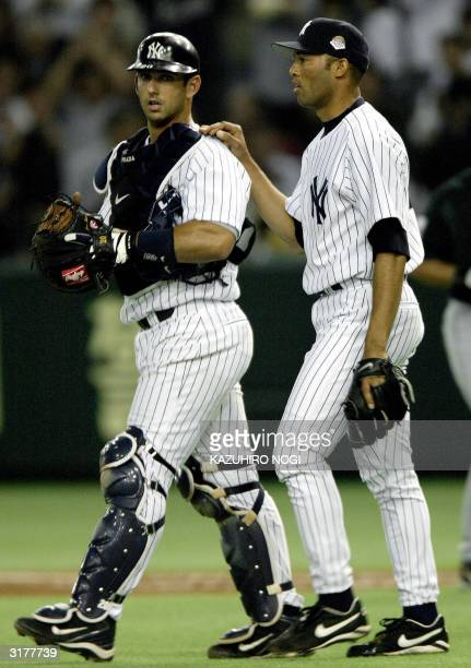 New York Yankees relief pitcher Mariano Rivera and catcher Jorge Posada celebarte their victory after the second game of the Major League Baseball...